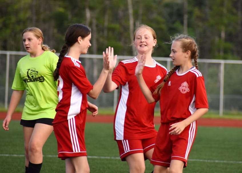 Rhysa Marinelli of Riverview, middle, gets a high-five from teammates Rachel Moore, left, and Carly MacLean after scoring a goal during Cape Breton and District Soccer League under-13 girls' quarterfinal action at Cape Breton Health Recreation Complex on Friday. Riverview won the game 4-0. JEREMY FRASER/CAPE BRETON POST. - Jeremy  Fraser