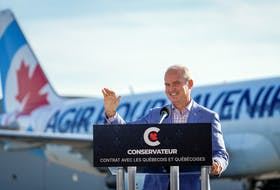 Conservative Leader Erin O'Toole waves during a speech at Chrono Aviation during his election campaign tour in Quebec City on Aug. 18, 2021.