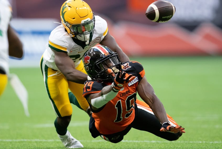 B.C. Lions' Dominique Rhymes (19) dives but fails to make the reception as Edmonton Elks linebacker Darius Williams defends in Vancouver on Thursday Aug. 19, 2021.