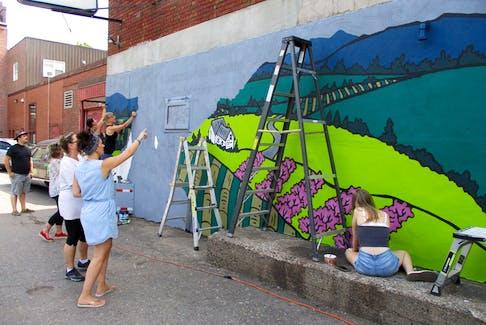 Jaimie Peerless of Phantom Studio talks to one of her helpers as the mural in homage to Theresa McAuley Robinson takes shape behind Main Street Station in Kentville.