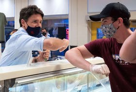 Justin Trudeau, elbow taps with a staff member at the Cows Creamery in Charlottetown, Prince Edward Island, during campaigning Aug. 22, 2021.