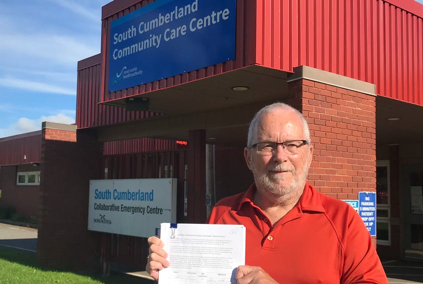 Bruce Lantz holds a copy of a petition calling for the reopening of the emergency department in front of the South Cumberland Community Care Centre in Parrsboro. The hospital's ER has been closed since March 2020 with no indication on when, or if, it will reopen.