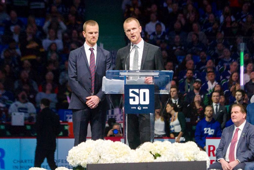 Henrik Sedin speaks at the podium with brother Daniel (left), a seated Canucks general manager Jim Benning (right) and a capacity crowd at Rogers Arena, as Vancouver celebrated a tribute night to the retired twins on Feb. 12, 2020. Daniel says he has a lot of appreciation for how hard Benning works the phones in his job.