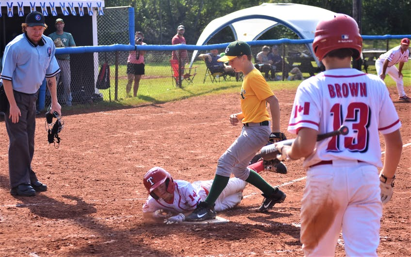 Curtis Weatherby slides head-first into home to score a run on a wild-pitch versus the Hammonds Plains A's in round-robin action. - Richard MacKenzie