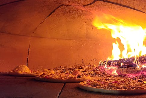 The wood-fired oven in the Sticks and Stone food trailer produces a rich-tasting pizza that is cooked in just a few minutes at a temperature around 800° F.