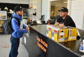 Customer Kyle MacInnis, left, talks business with Cape Breton Liquidator owner Mike Ranni at the upper George Street, Sydney establishment. DAVID JALA • CAPE BRETON POST