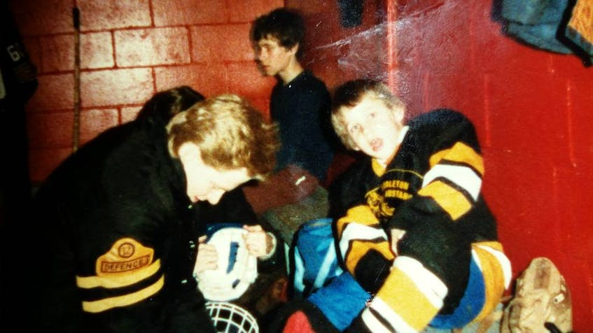 James Peppard helps a young Cail MacLean with his skates. - Contributed