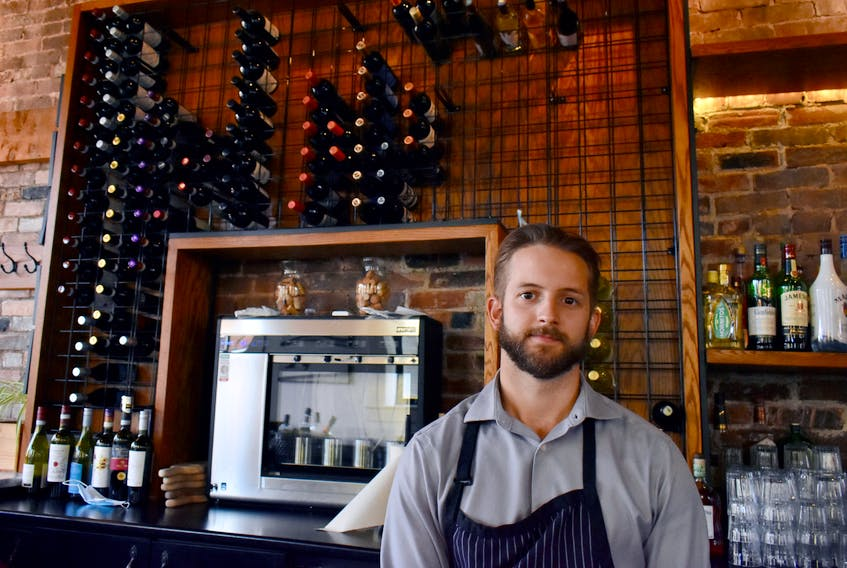 Daniel Good, manager at Piatto Pizzeria and Enoteca in Charlottetown, stands in front of a dwindling supply of wines. Though the restaurant hasn't been keeping as much stock on hand since the pandemic started, in the last month shortages have been keeping shelves even more bare.
