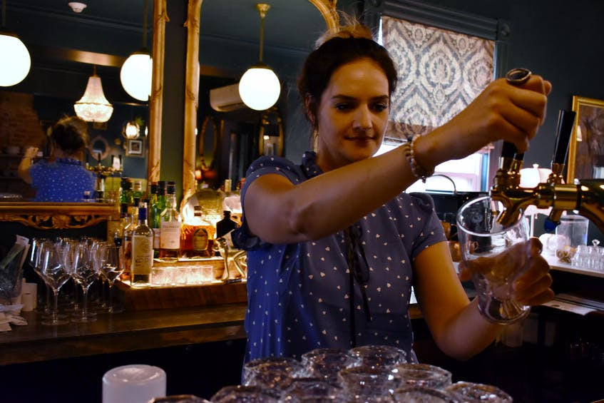 Maggie Wright, manager at Slaymaker and Nichols, readies a glass at one of the beer taps in the restaurant on Aug. 25. Though beer has been affected by worldwide shortages, wine has been the product most affected recently. - Michael Robar • The Guardian