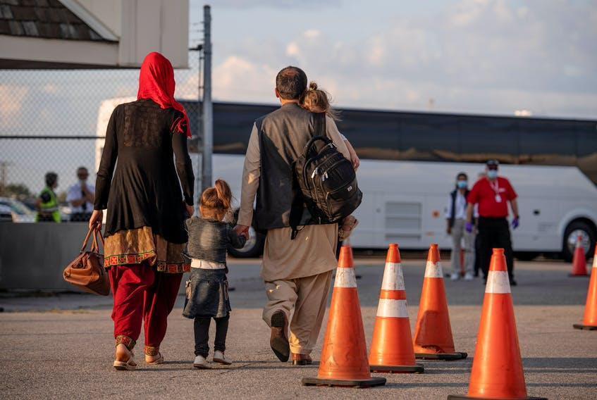 Afghan refugees who supported Canada's mission in Afghanistan prepare to board buses after arriving in Canada at Toronto Pearson International Airport on Tuesday, Aug. 24, 2021. - Master Cpl. Genevieve Lapointe / Canadian Forces Combat Camera via Reuters
