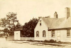 A.C. Dodd's residence on the corner of Dorchester Street and the Esplanade in Sydney, known as Judge's Corner.  Two members of the Dodd family stand at the gate. The second building in the picture was used as a ballroom. Contributed • Beaton Institute, Cape Breton University