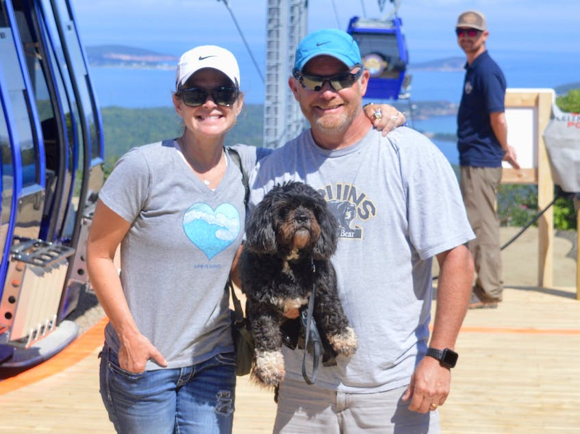 Lori and Tim Kruger were among the first passengers to ride the new gondola lift at the Destination Cape Smokey resort in Ingonish. Ozzy the dog is accompanying the Halifax couple on their Cape Breton visit. Lift attendant Erik Fullerton is in the background. DAVID JALA/CAPE BRETON POST
