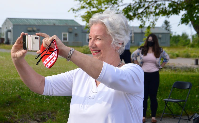 Cape Breton native and renowned Canadian businesswoman Annette Verschuren not only makes news – she also likes to be there when it happens. Verschuren, who is being inducted into the Cape Breton Business and Philanthropy Hall of Fame for a second time, is shown above taking pictures at a recent solar energy project announcement at the site of the former Canadian Forces Base Sydney. DAVID JALA/CAPE BRETON POST - David Jala