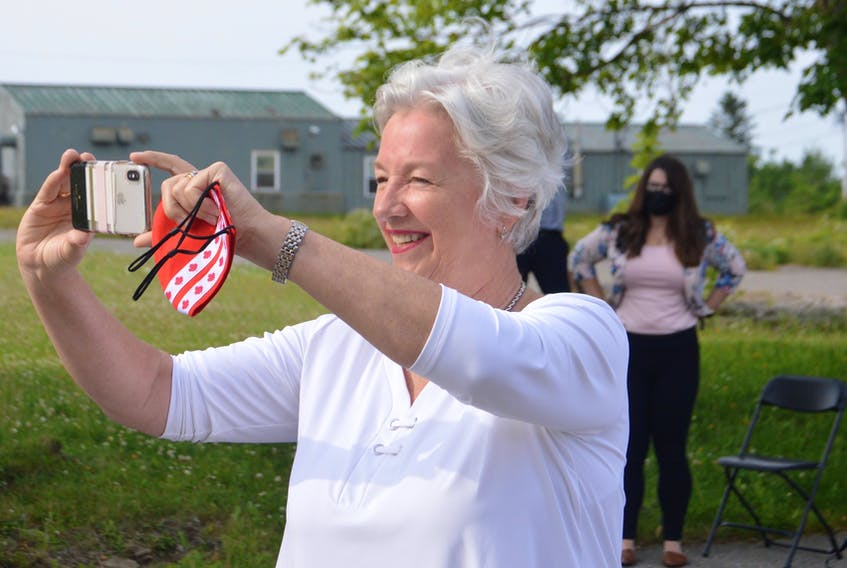 Cape Breton native and renowned Canadian businesswoman Annette Verschuren not only makes news – she also likes to be there when it happens. Verschuren, who is being inducted into the Cape Breton Business and Philanthropy Hall of Fame for a second time, is shown above taking pictures at a recent solar energy project announcement at the site of the former Canadian Forces Base Sydney. DAVID JALA/CAPE BRETON POST