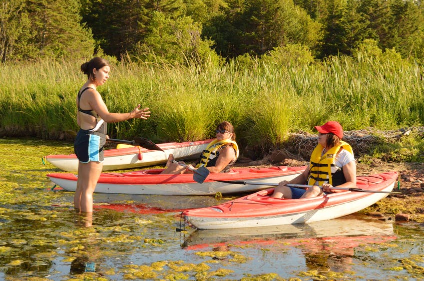 A go!P.E.I. employee, left, gives some pointers to kayakers Faye MacWilliams and Geraldine MacKendrick at the Roseville Pond Natural Area Aug. 9. - Alison Jenkins