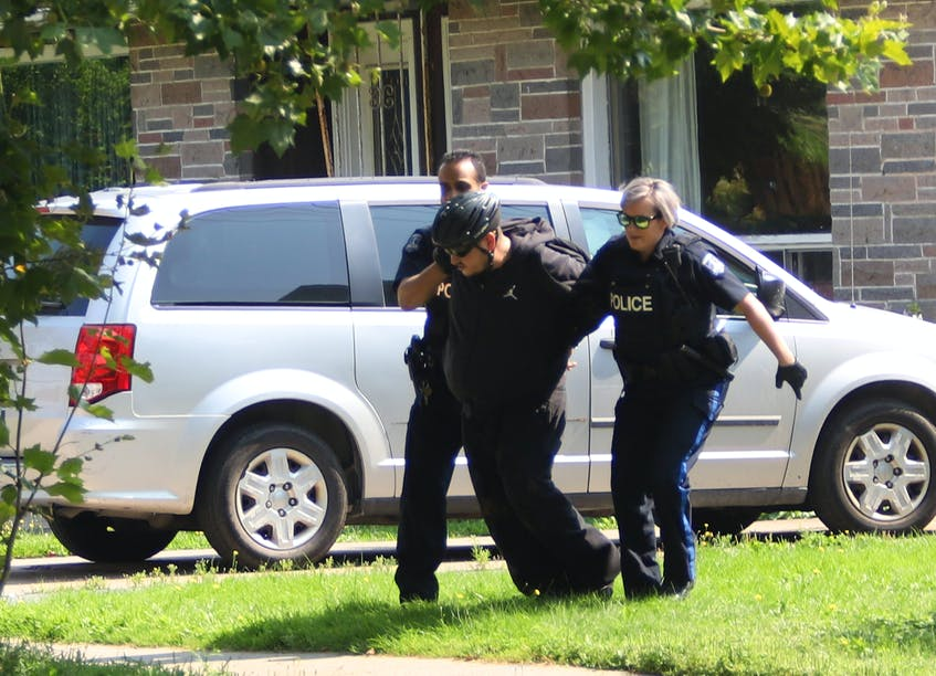 Halifax Regional Police officers take a suspect into custody from behind a home on Albro Lake Road in Dartmouth, Friday Aug. 27, 2021. - Tim Krochak
