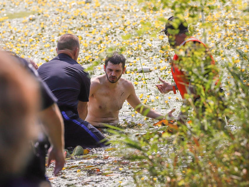 Halifax Regional Police officers prepare to take a suspect into custody after pulling him to safety from a weed-filled Little Albro Lake in Dartmouth, Friday, Aug. 27, 2021. - Tim Krochak