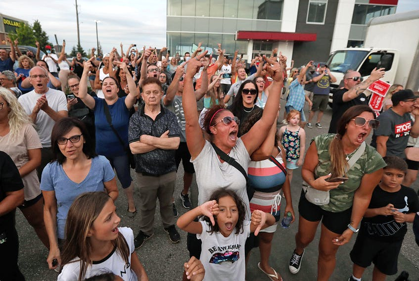 Protestors react following the cancellation of a campaign event for Liberal Leader Justin Trudeau in Bolton, Ontario, August 27, 2021.