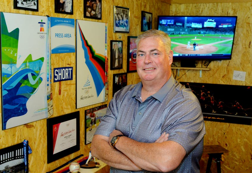 Robin Short in his man-cave garage, surrounded by press credentials and other memorabilia he collected during a career in sports journalism spanning 36 years. Short, The Telegram's long-time Sport Editor, died Aug. 29 at 56. — Telegram file photo/Joe Gibbons - Joseph Gibbons