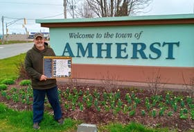 Randy Hicks holds up a brochure celebrating Amherst's African Nova Scotian heritage in front of the Town of Amherst sign on South Albion Street.