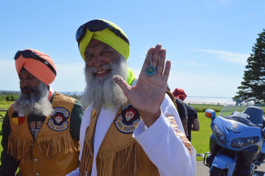 Randhir Singh dhanda, left, Malkiat Singh hoonjan and the riders were gifted souvenir keychains from the P.E.I. Sikh Association. - Alison Jenkins/Special to SaltWire