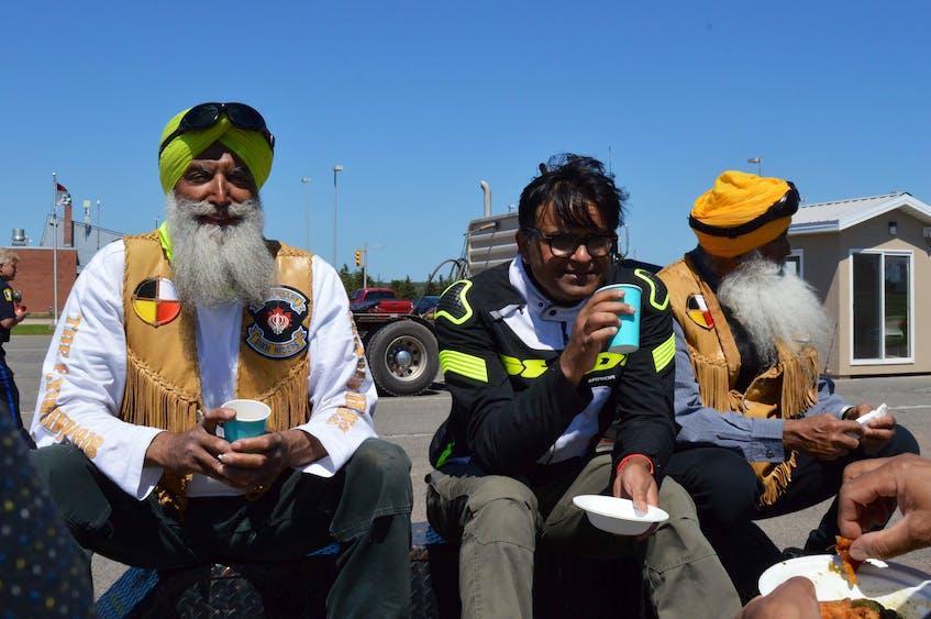 Legendary Sikh Rider Malkiat Singh hoonjan, left, photographer Vivek Sharma and Legendary Sikh Rider Dalel Singh brar enjoy some chai in Borden-Carleton Aug. 3. - Contributed