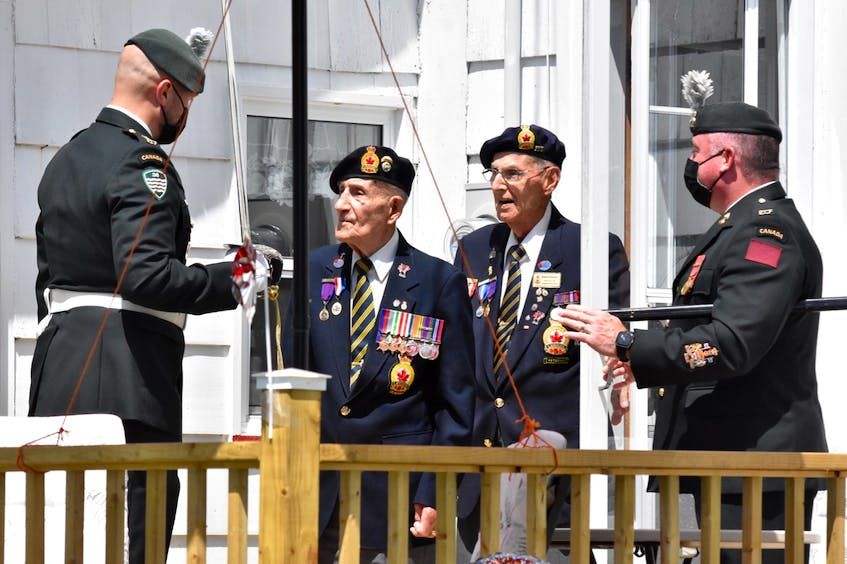 Charlie Muise is greeted at his door. Standing behind him is Second World War veteran Roland Bourque. TINA COMEAU PHOTO