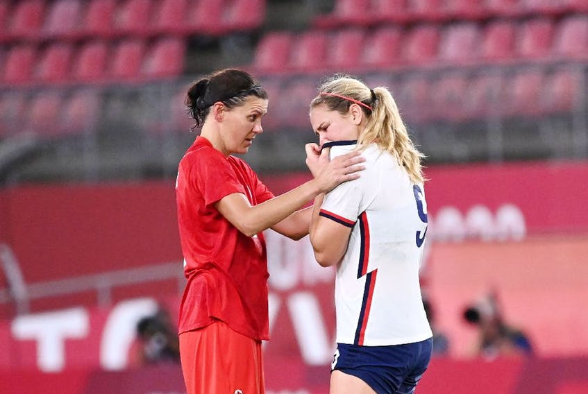 Canada's forward Christine Sinclair (L) comforts USA's midfielder Lindsey Horan after the Tokyo 2020 Olympic Games women's semi-final football match between the United States and Canada at Ibaraki Kashima Stadium.