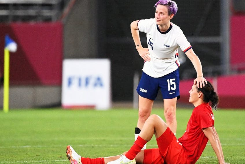 Forward Megan Rapinoe (C) congratulates Canada's midfielder Jessie Fleming after the Tokyo 2020 Olympic Games women's semi-final football match between the United States and Canada.