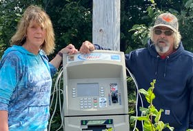 """Dennis Day and his girlfriend, Pam Fitzgerald, stand next to the ATM Day has set up at the end of his driveway along the Cabot Trail in Cape North. """"I've always been somewhat of a prankster,"""" said Day, a heavy-equipment operator and hunting guide."""