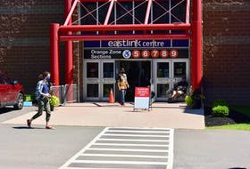 A worker stands outside the Eastlink Centre in Charlottetown to check Islanders into the COVID-19 vaccination clinic. The clinic will be closing at this location later in August.