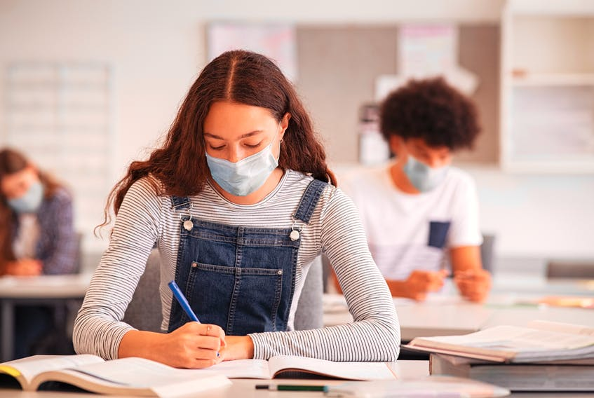 High school students take notes while wearing face masks in the classroom.
