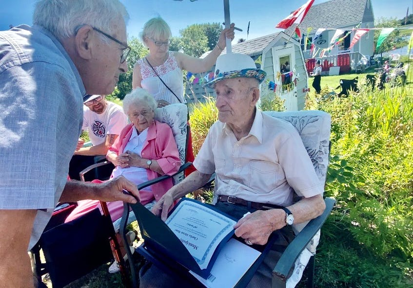 As his wife Annie of 79 years looks on, Second World War veteran Charlie Muise receives congratulations on turning 100 from Argyle Warden Danny Muise. A surprise birthday parade was held for Muise on Aug. 1. TINA COMEAU • TRICOUNTY VANGUARD
