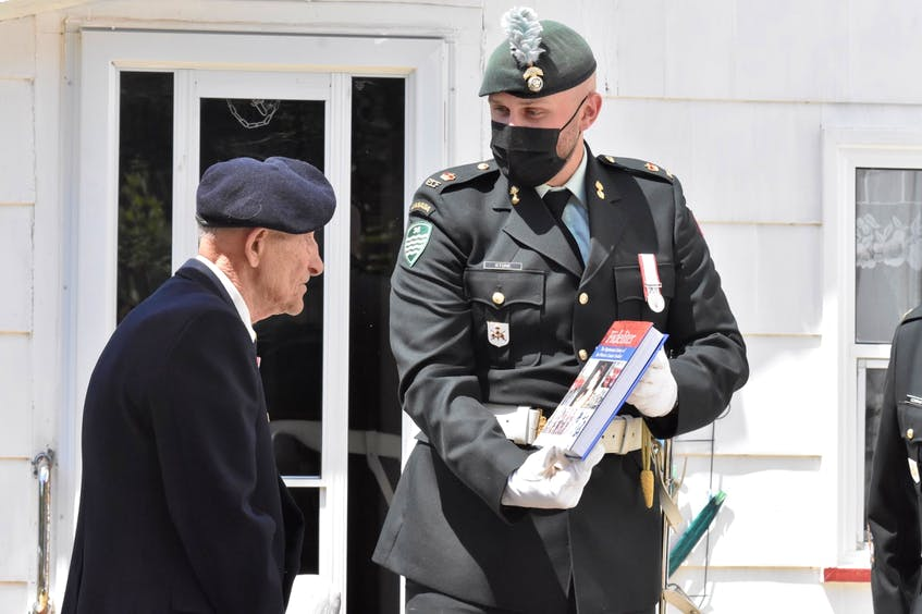 Major Kevin Stone of the Princess Louise Fusiliers – the regiment that Second World War veteran Charlie Muise belonged to during the war – presents him with a book written about the regiment, and signed by the author, on his 100th birthday on Aug. 3. TINA COMEAU • TRICOUNTY VANGUARD