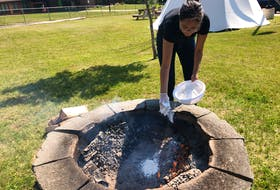 Kelly Sark covers bannock with flour as she places it in the fire to cook at the Lennox Island FIrst Nation's guided experience called Bannock and Clams on the Sand at the Mi'kmaq Culture Centre. Indigenous tourism - once a fast-growing sector - has been hard hit by the pandemic. - Helen Earley