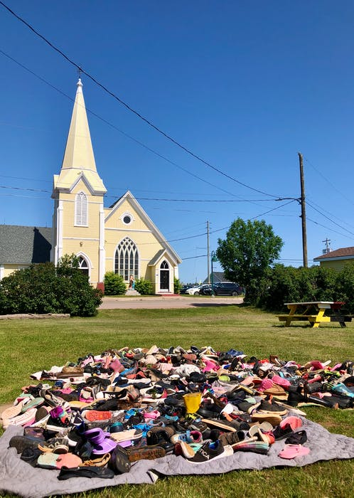 With St. Anne's church in the background, 215 pairs of shoes, placed on a blanket, represent the 215 children whose remains were found in Kamloops, British Columbia in May 2021. There have since been hundreds of more burial sites discovered on former residential school sites across the country. - Helen Earley - Saltwire network