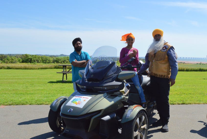 Savneet Singh, left, stands nearby as daughter Ajooni Kaur tries out Legendary Sikh Rider Dalel Singh Brar's motorcycle in North Carleton on Aug. 3.  Alison Jenkins • Special to The Guardian