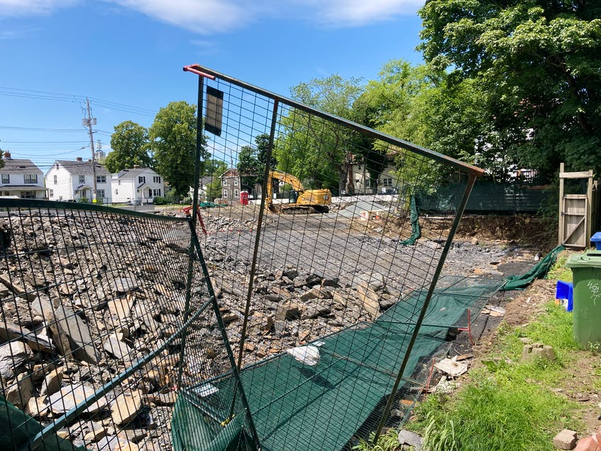 The construction fence bordering sidewalks and homes has repeatedly collapsed through various stages of the construction project. - Andrew Rankin