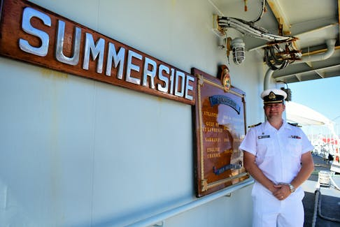 """Lt.-Cmdr. Jeffrey Anderson stands next to the HMCS Summerside's honours and awards. At the plaque's end is the vessel's motto that reads, """"spem successus alit"""" (success nourishes hope.)"""
