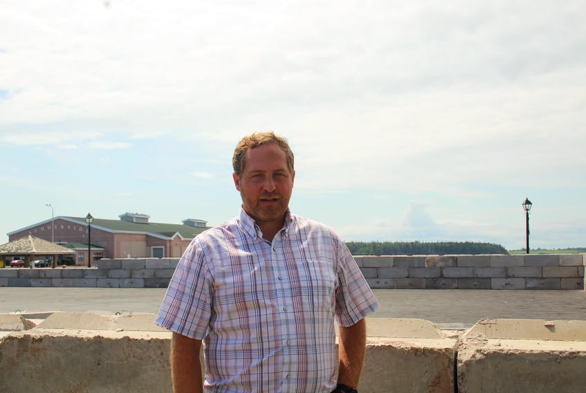 Summerside councillor Cory Snow stands in front of the structure being built downtown. The structure will be used to store 44,000 tonnes of road salt in the winter.