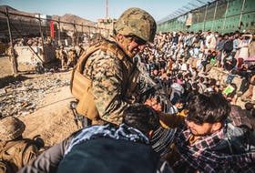A U.S. marine assists at an evacuation control checkpoint during an evacuation at Hamid Karzai International Airport on Aug. 26 in Kabul, Afghanistan. U.S. Marine Corps/Staff Sgt. Victor Mancilla/Handout via REUTERS