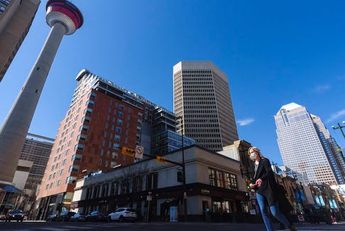A masked pedestrian crosses the Centre Street in downtown Calgary on Friday, April 16, 2021.