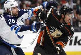 Michael Del Zotto, then a member of the Anaheim Ducks, battles Winnipeg's Blake Wheeler in October 2019.
