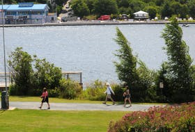 People walk on the path around Quidi Vidi Lake in St. John's on Aug. 4, as the pond and pondside were quiet Wednesday due to the Royal St. John's Regatta not being held because of forecast high wind. No vendors are permitted at this year's event — again due to the COVID-19 pandemic — and spectators have been advised against attending and urged to watch the races on TV at home. Weather permitting, the 203rd running of the regatta will go ahead today, Aug. 5. JOE GIBBONS • THE TELEGRAM