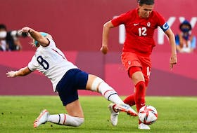 USA's midfielder Julie Ertz (L) tackles Canada's forward Christine Sinclair during the Tokyo 2020 Olympic Games women's semi-final football match between the United States and Canada at Ibaraki Kashima Stadium in Kashima on August 2, 2021.