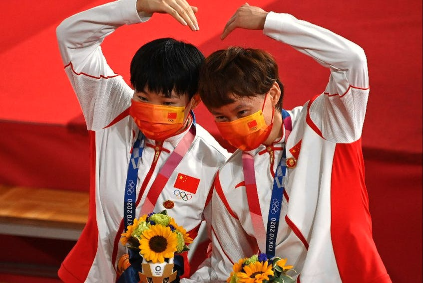 China's Bao Shanju (L) and Zhong Tianshi pose with their gold medals on the podium after the women's track cycling team sprint finals.