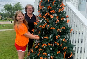 Cathy Halliday and her grandniece Melissa Sherwood-Gerow stand next to a tree with orange ribbons decorated as a tribute to our nation's Indigenous communities impacted by the recent discoveries of graves at former residential school sites. CONTRIBUTED