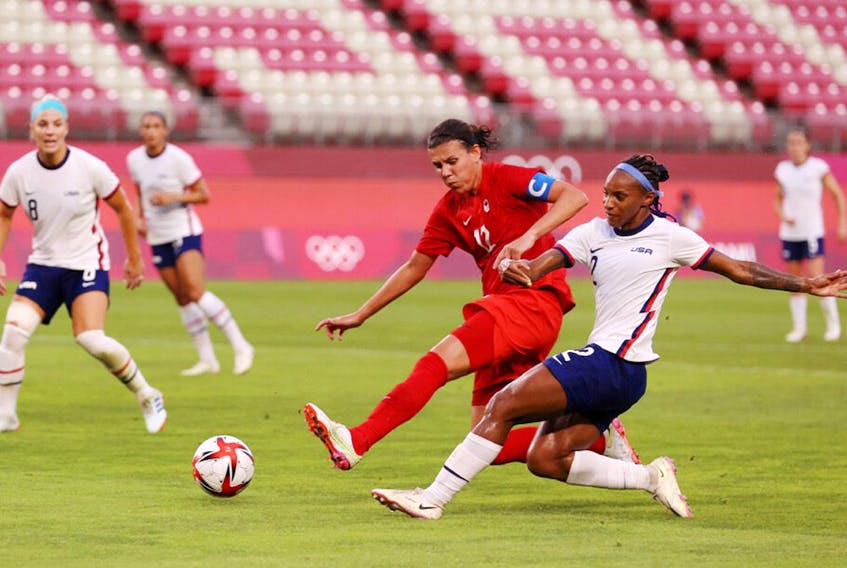 KASHIMA, JAPAN – AUGUST 02: Crystal Dunn #2 of Team United States shoots whilst under pressure from Christine Sinclair #12 of Team Canada during the Women's Semi-Final match between USA and Canada on day ten of the Tokyo Olympic Games at Kashima Stadium on August 02, 2021 in Kashima, Ibaraki, Japan.