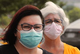 Two women wear masks Friday, Aug. 6, while attending a rally protesting the ferry service to Bell Island, at the Confederation Building in St. John's. Chief Medical Officer of Health Dr. Janice Fitzgerald announced Friday that as of 12:01 a.m. Tuesday wearing masks in public places will no longer be mandatory. JOE GIBBONS • THE TELEGRAM