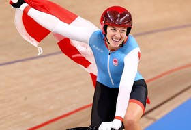 Kelsey Mitchell of Canada celebrates with a national flag after winning gold in the cycling sprint at the Izu Velodrome in Shizuoka, Japan, on Aug. 8, 2021.